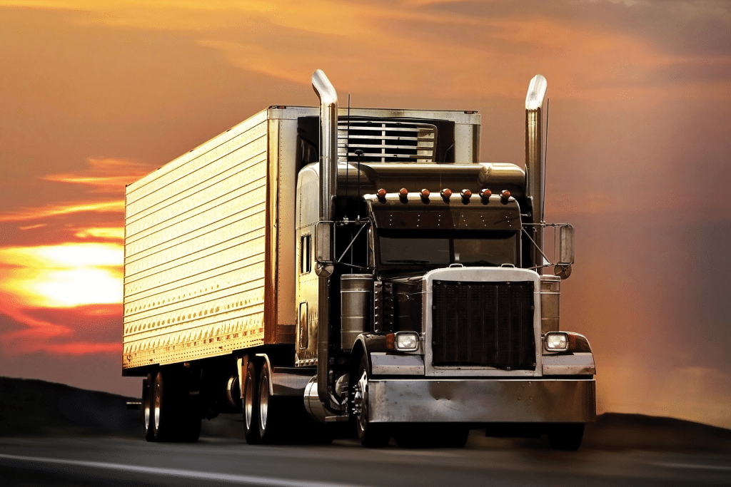 Black commercial semi-truck vehicle driving away from the setting sun leading in innovation and delivery